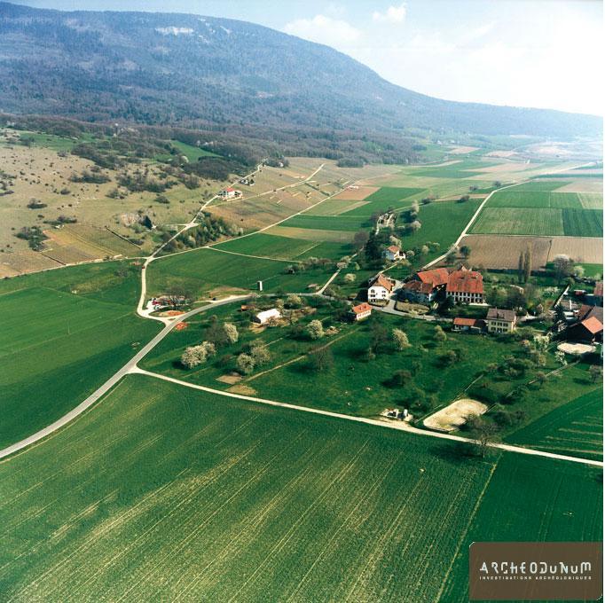 Onnens - Vue générale de la première tente de fouilles. A droite, le village d'Onnens. A gauche, la base archéologique (Photo J. Jeker) Photoconstruction,