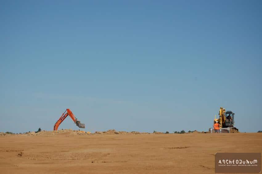 Décapage en cours. Le site se présente sous la forme d'un plateau en bordure duquel s'amorce un petit vallon depuis lequel est prise la photo.