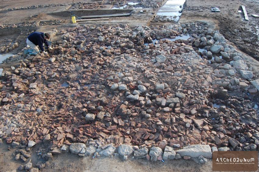 Une pièce semi-enterrée antique est comblée par l'effondrement de sa toiture.