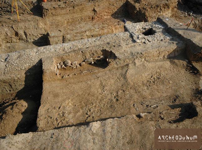 Vue du regard et d'une partie du conduit de l'aqueduc avec, au premier plan, trois tombes de la nécropole de l'Antiquité tardive.