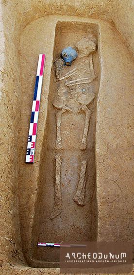 Fareins - Sépulture 81 : Une cruche en céramique, un bracelet en bronze et une monnaie accompagnent le corps dans le cercueil