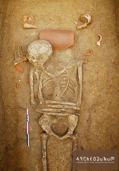 Fareins - Sépulture 88 : La tête du défunt repose sur une imbrex, tandis qu'un petit gobelet et une coupelle contenant une pièce de viande ont été déposés sur le cercueil.
