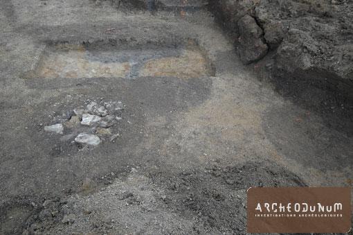 Système de bassins en bois alimentés par une canalisation (à l'arrière plan). Ces structures sont recoupés par un puits (à gauche).
