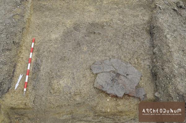 Vue d'une plaque foyère (dalle de molasse) déposée au fond d'une fosse (fin du Moyen Âge/début de l'Époque moderne).